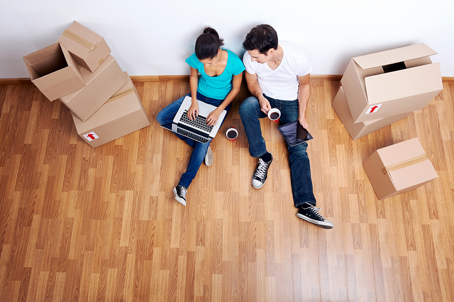 overhead view of couple sitting on floor together using computer wireless internet while moving into new home