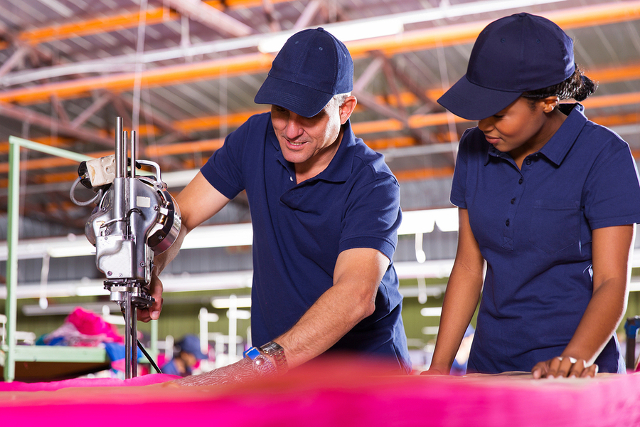 senior textile worker teaching new employee about cutting materi