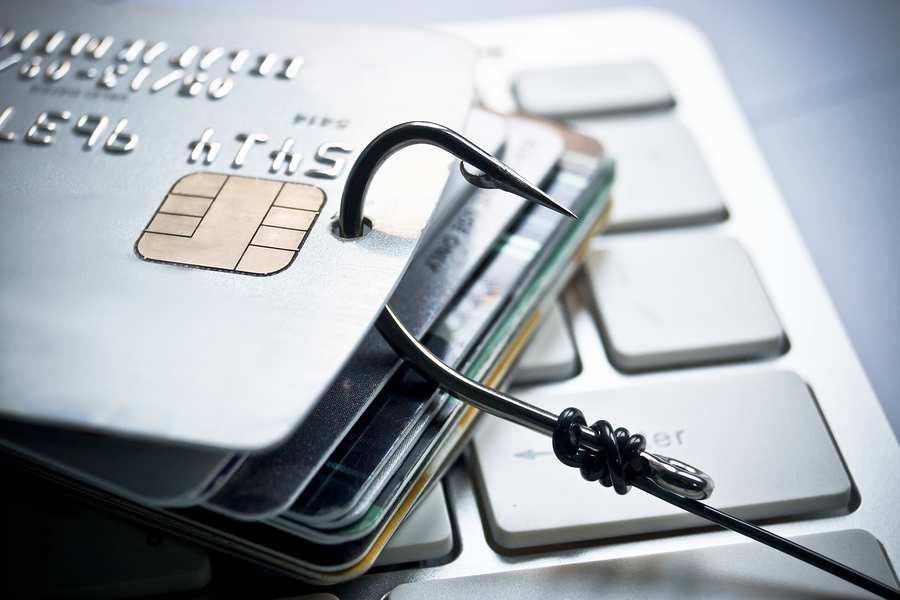 a fish hook on piles of credit cards over computer keyboards - phishing concept
