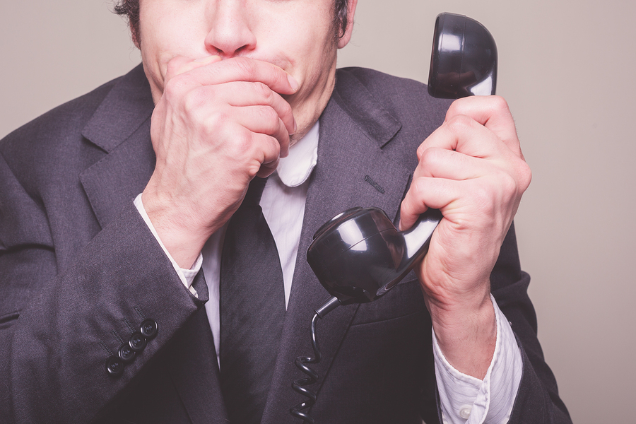 A young businessman is on the phone and covering his mouth in shock