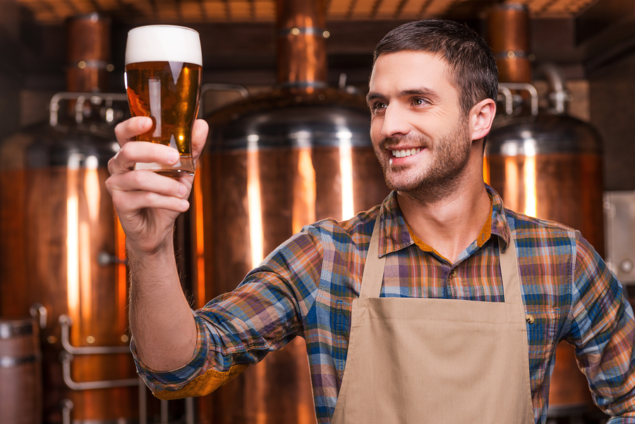 Happy young male brewer in apron holding glass with beer and looking at it with smile while standing in front of metal containers