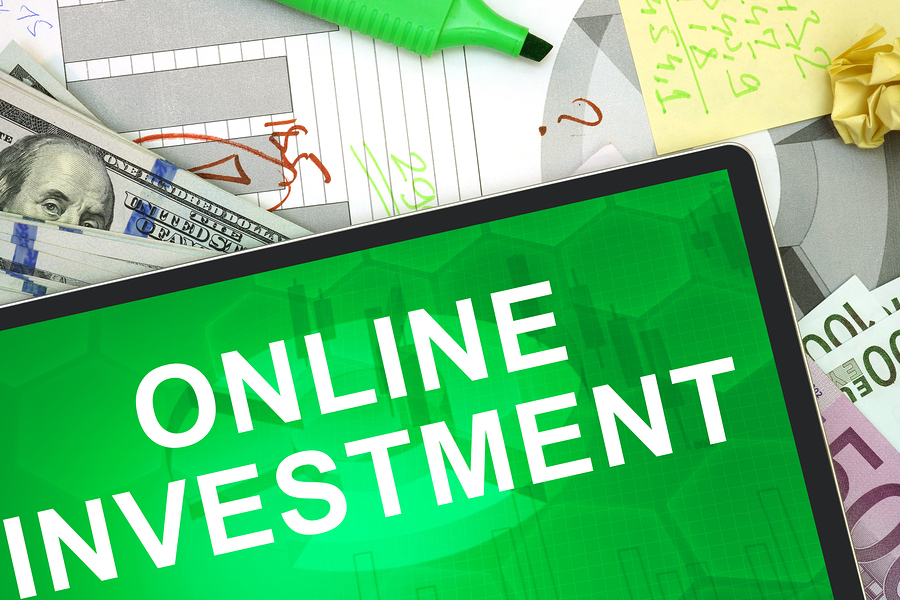 Tablet with words online investment with dollars and euro. Business concept
