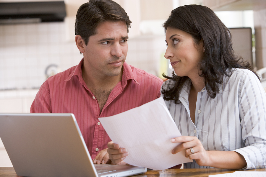 Couples In Kitchen With Paperwork Using Laptop Looking Unhappy