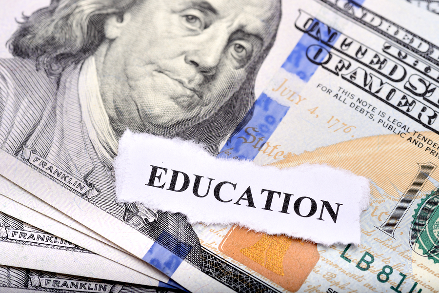 Education loan concept with dollar note and paper on foreground