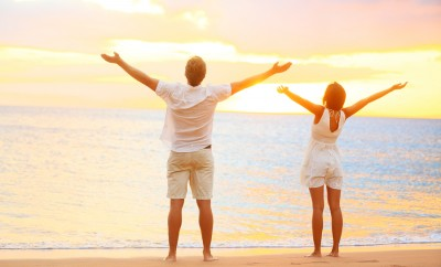 Happy cheering couple enjoying sunset at beach with arms raised up in joyful elated happiness. Happi