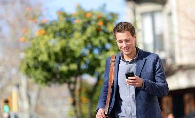 Young urban professional man using smart phone. Businessman holding mobile smartphone using app text