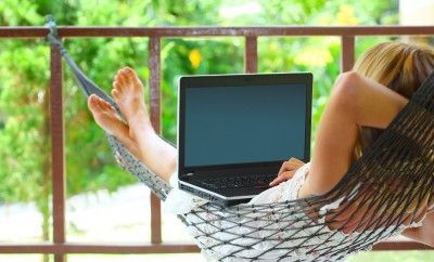 Young woman sitting in a hammock in a garden with laptop