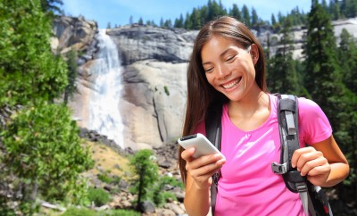 Smartphone - woman hiker using smart phone app on travel hike living healthy active lifestyle by wat